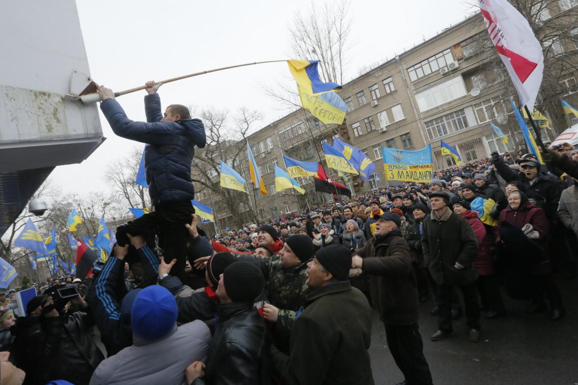 Demonstranti umisťují ukrajinskou vlajku na sídlo ministerstva vnitra