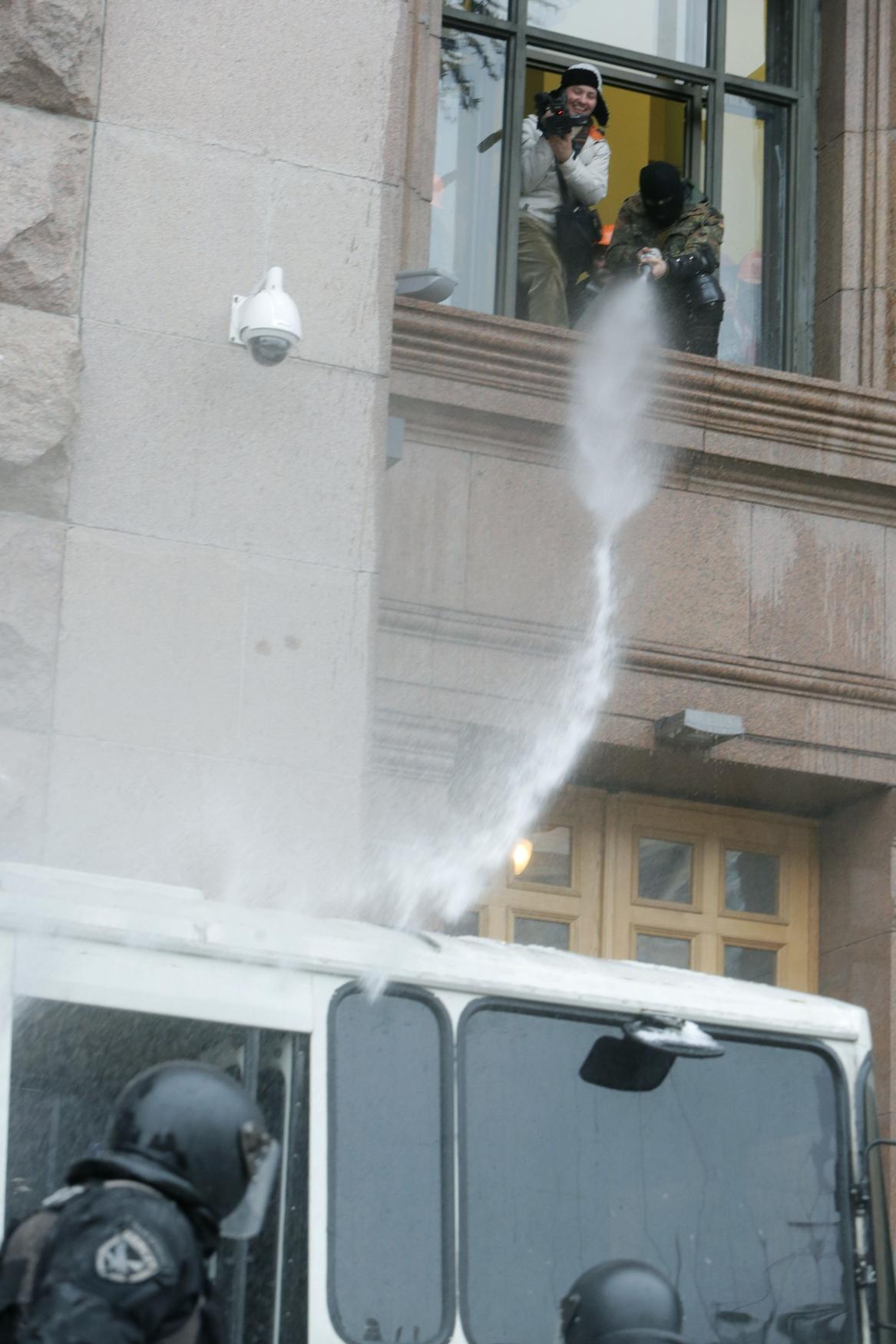 Demonstranti lijí z kyjevské radnice vodu na zasahující policisty