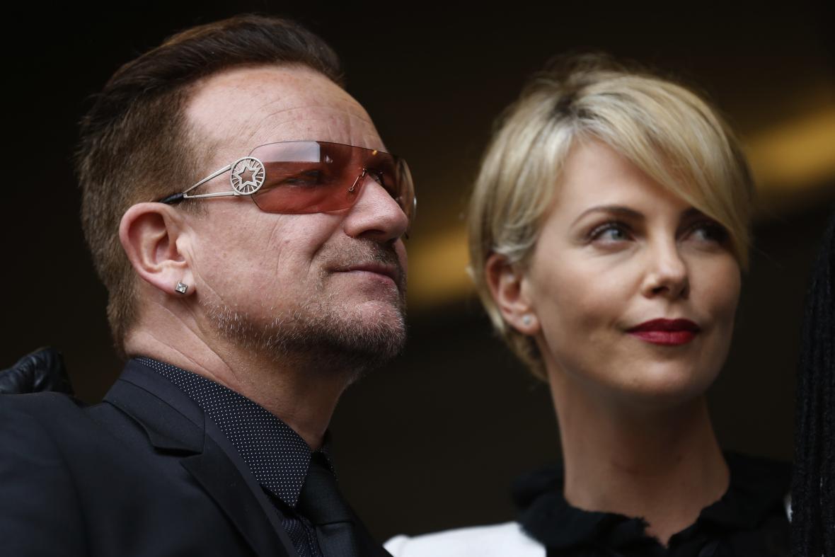 Hudebník Bono Vox a herečka Charlize Theron při zádušní mši