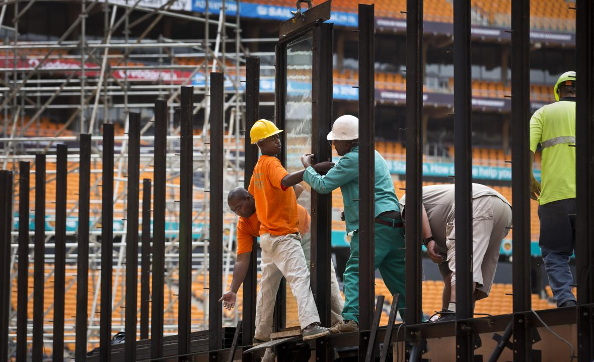 Pracovníci instalují neprůstřelné sklo, které bude obklopovat jeviště na stadionu
