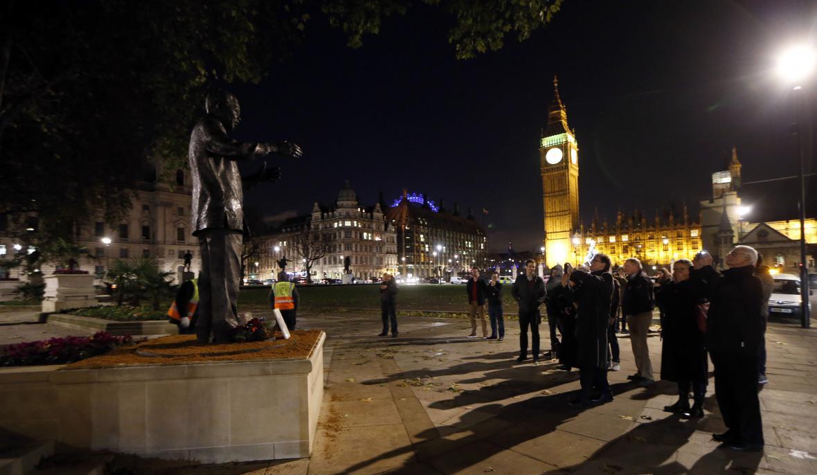 Lidé před sochou Nelsona Mandely na Parliament Square v Londýně