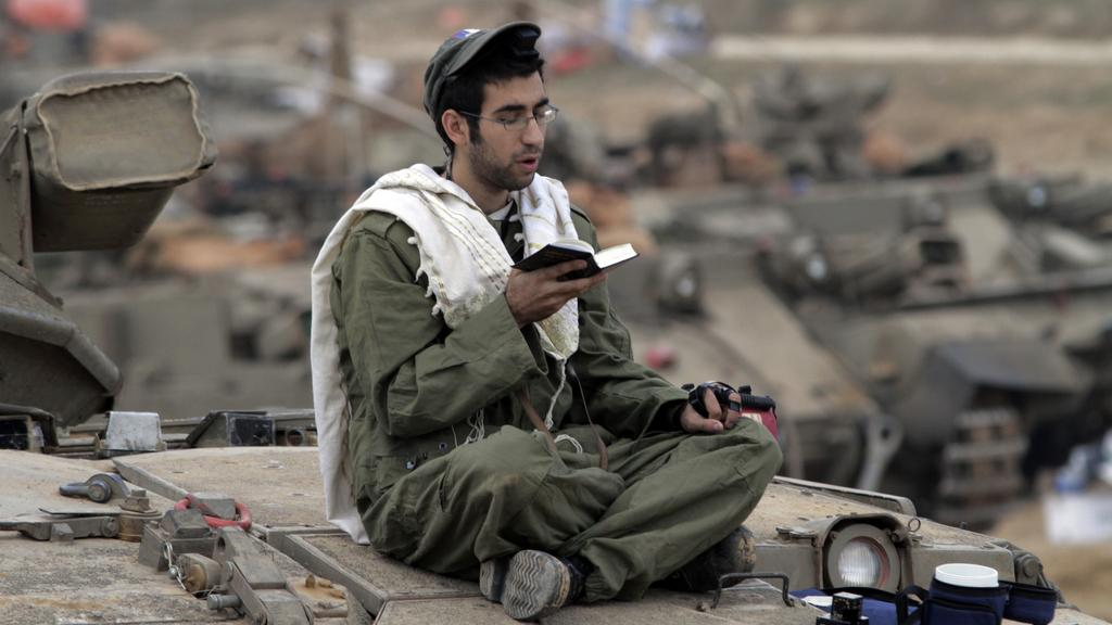Izraelský voják se modlí na svém tanku poblíž pásma Gazy