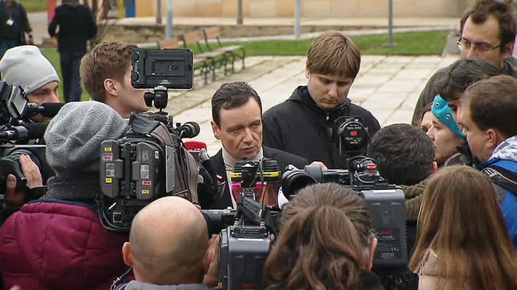 Rath mluví k novinářům na náměstí v Hostivici