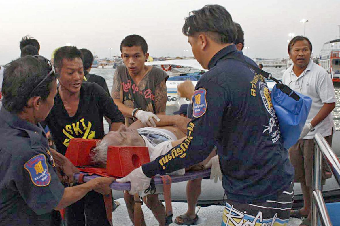 Thajští záchranáři se zraněným turistou z potopené lodi