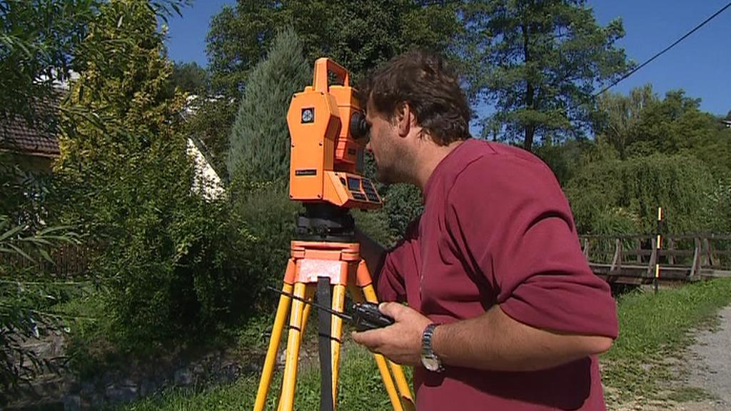 Geodet při zaměřování objektu