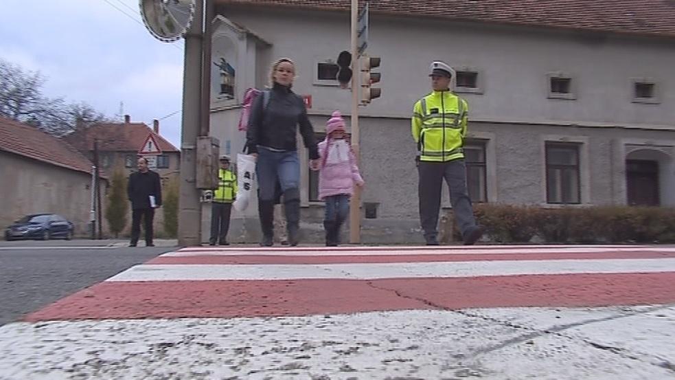 Policisté pomáhají dětem přecházet silnici