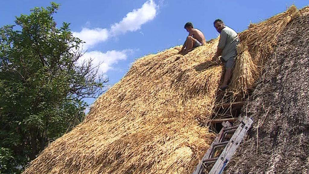 Doškář při práci na střeše