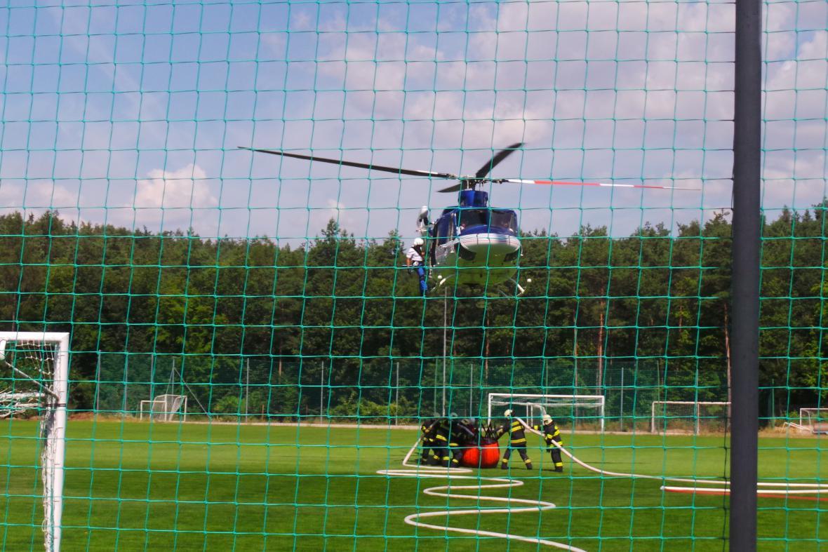 Vrtulník nabírá vodu na místním fotbalovém hřišti