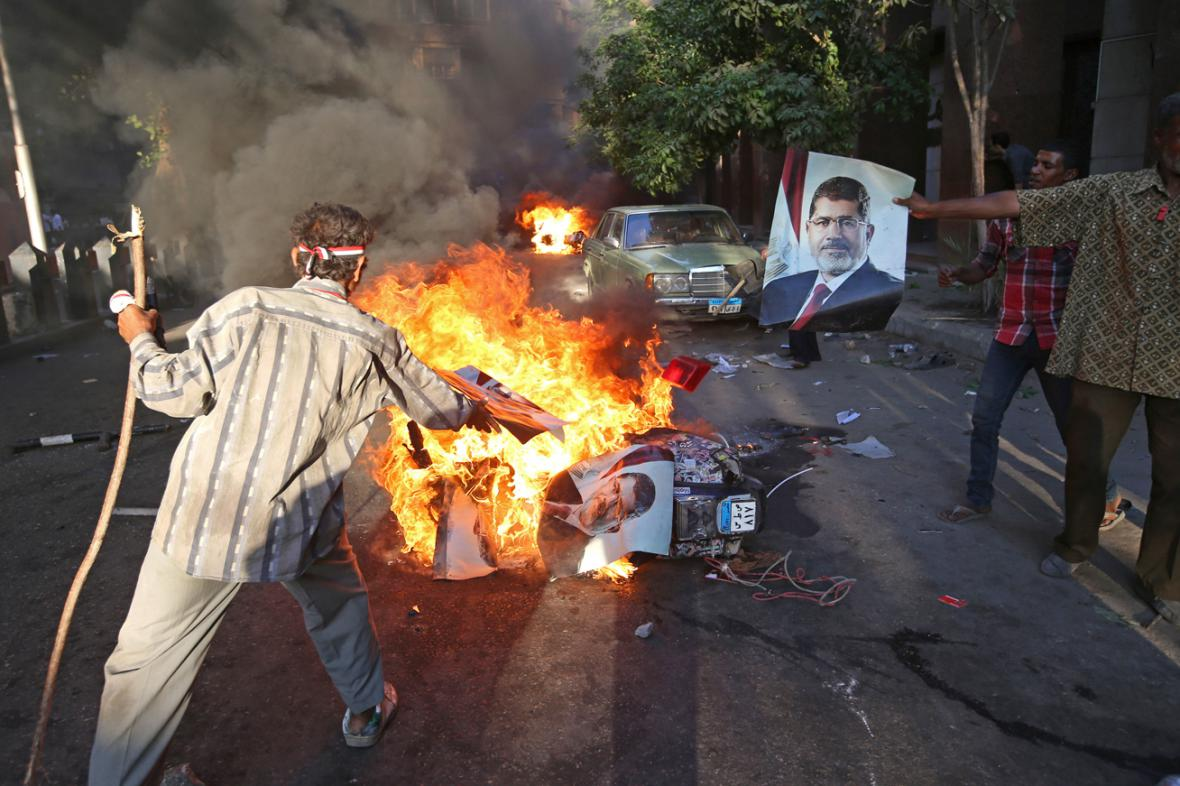 Odpůrci Mursího pálí portréty svrženého prezidenta