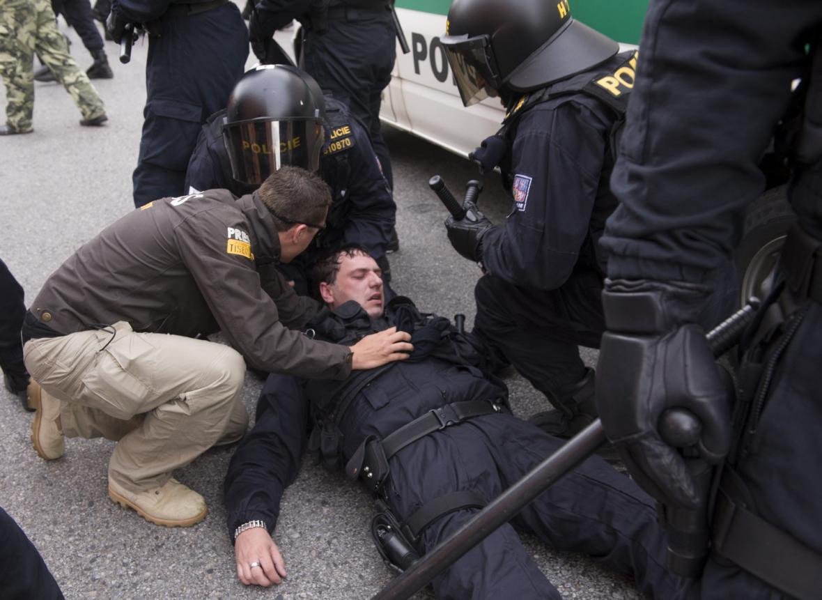 Zasažený policista po střetu pořádkové služby s demonstranty v ulici J. Bendy