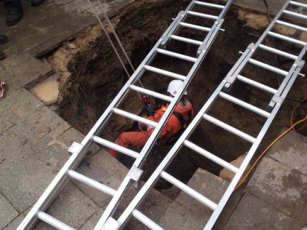 Záchranář slaňuje do studny