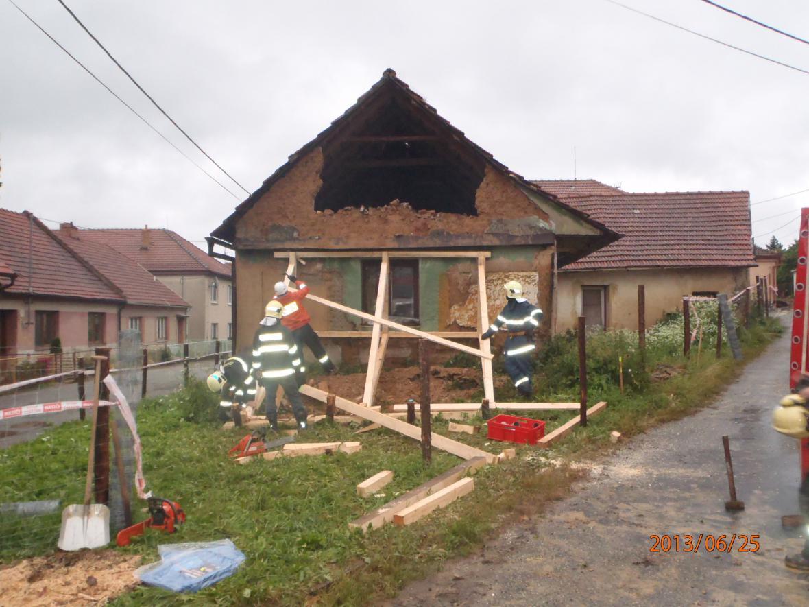 Hasiči podpírají zřícenou část domu