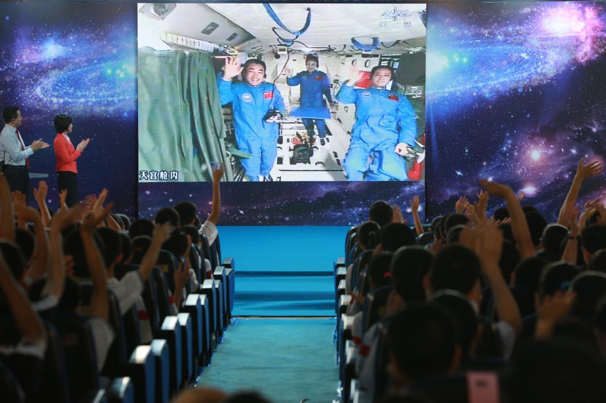 Studenti v Pekingu mávají kosmonautům na rozloučenou
