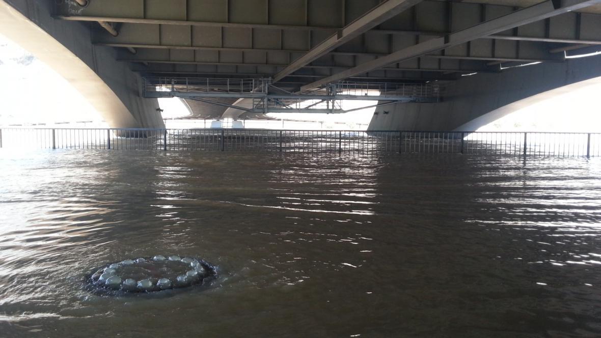 Stoupající voda vytéká pod Mariánským mostem z kanálů