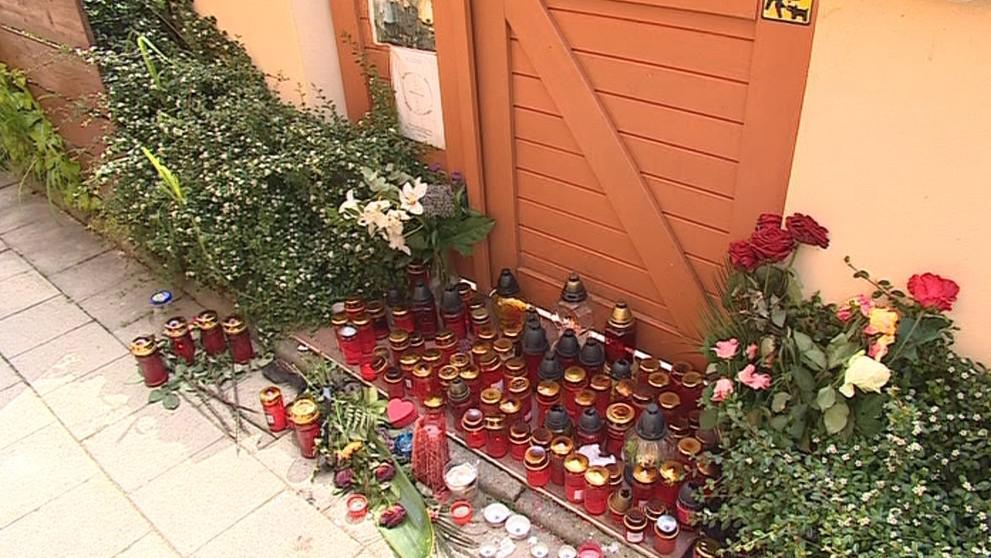 Před vchod do domu lidé stále pokládají květiny a svíčky