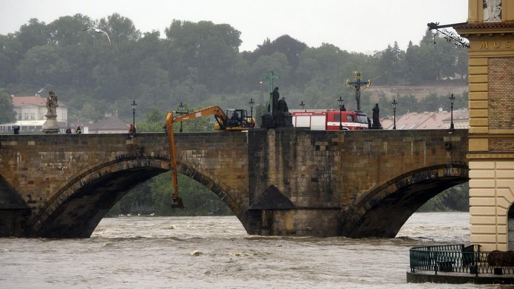 Bagr odklízí naplaveniny na uzavřeném Karlově mostě