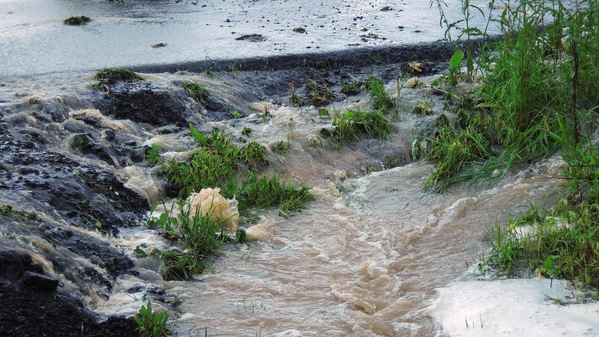 Voda z polí tekoucí přes silnici do škarpy, nedaleko Kadaně