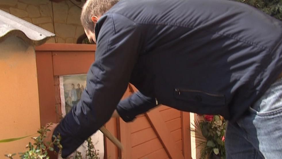 Kamarád jedné z obětí připevňuje na branku dopis
