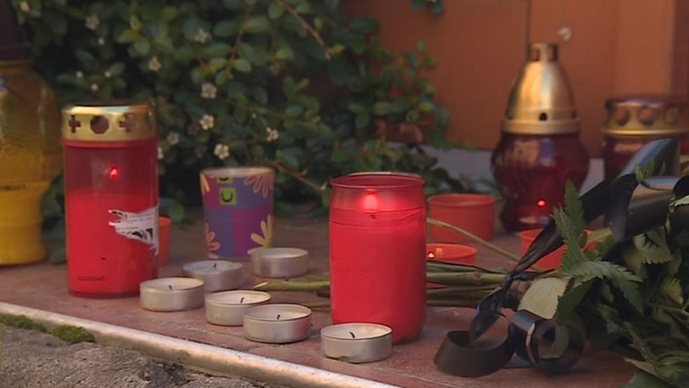 Lidé před dům pokládají květiny a zapalují svíčky