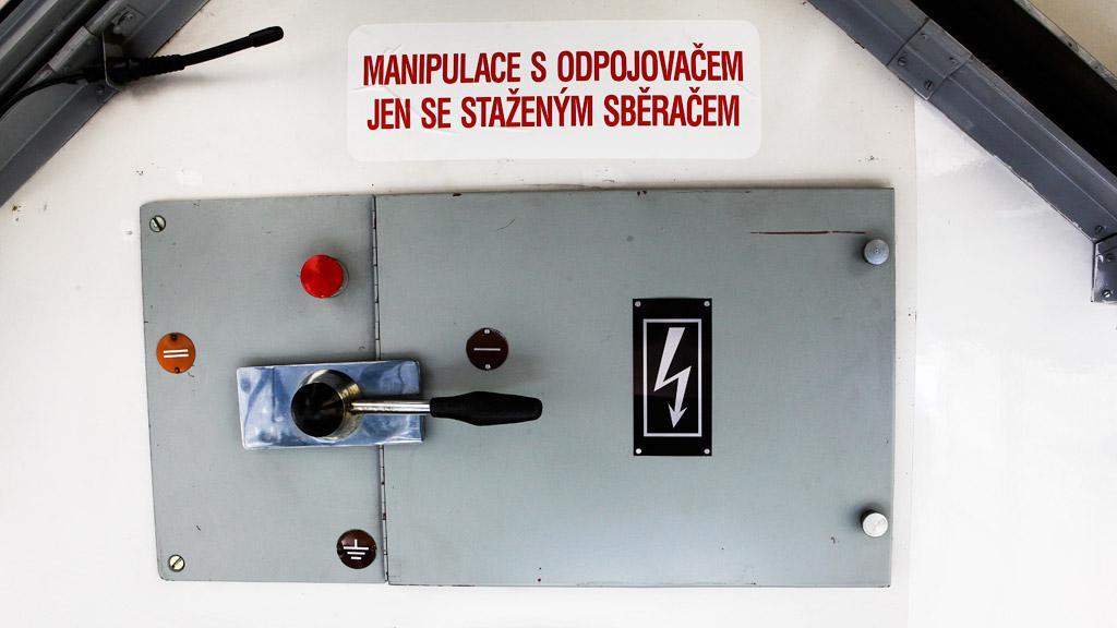 Páka pro manipulaci s odpojovačem-uzemňovačem proudu z pantografů na stropě každé ze dvou kabin řidiče na obou stranách