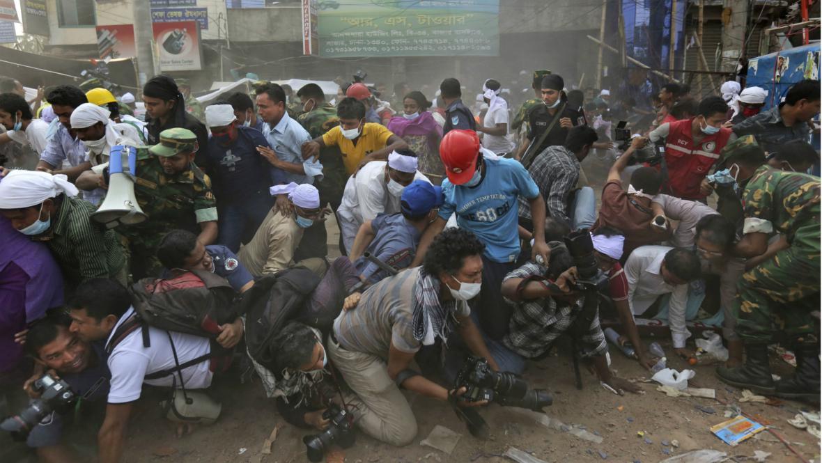 Novináři a přihlížející prchají z obavy před dalším pádem trosek od zřícené budovy