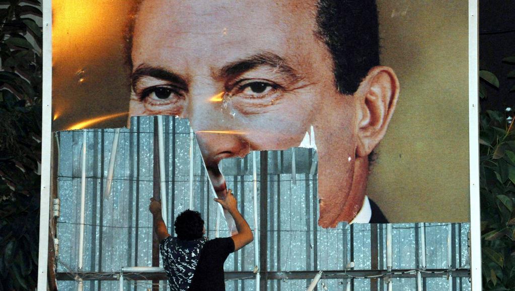 Demonstrant strhává plakát Mubaraka