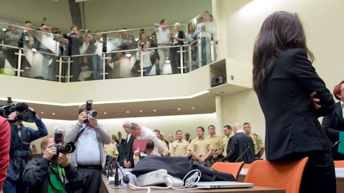 Soudní síň, obžalovaná stojí zády k novinářům