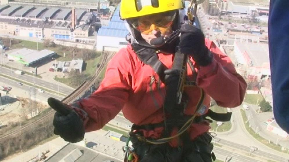 Záchranář se z vrtulníku spouští na střechu AZ Tower