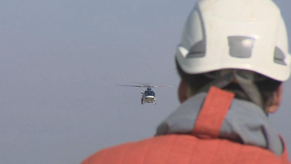 Záchranář vyhlíží ze střechy AZ toweru vrtulník