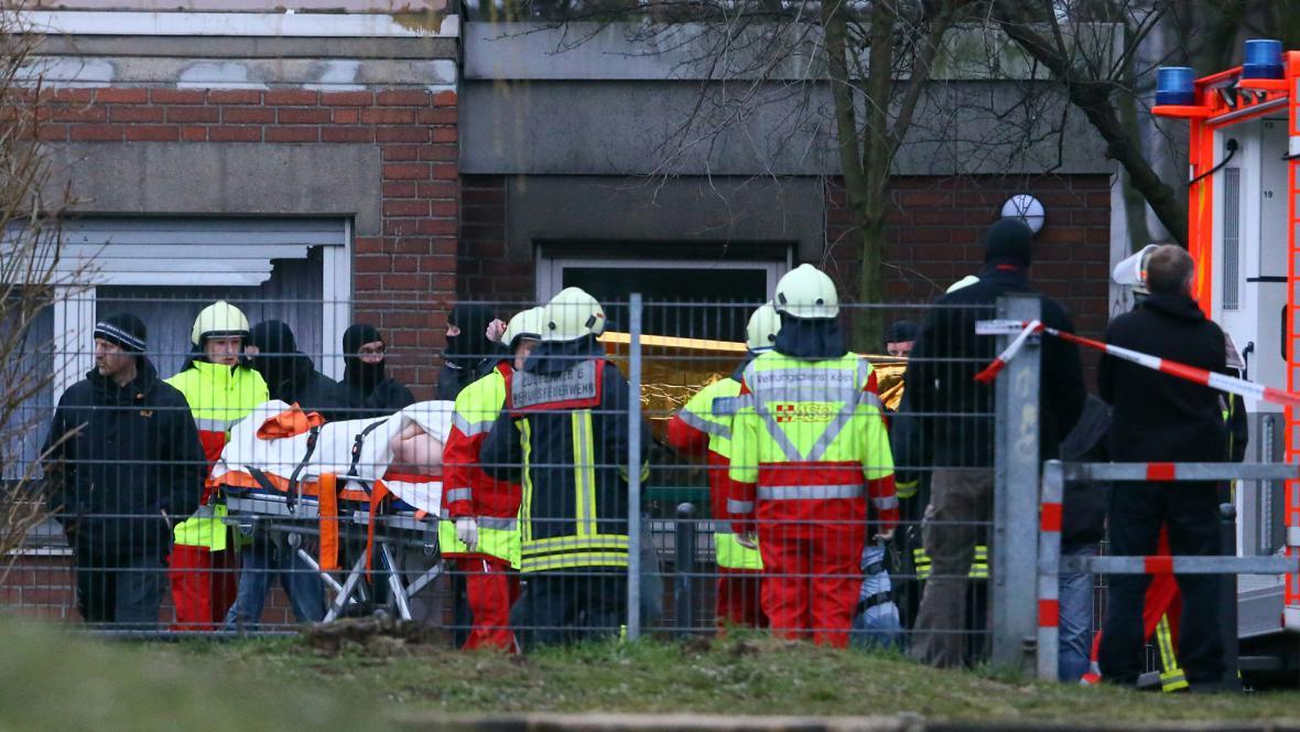 Záchranáři odvážejí zraněného po přepadení školky