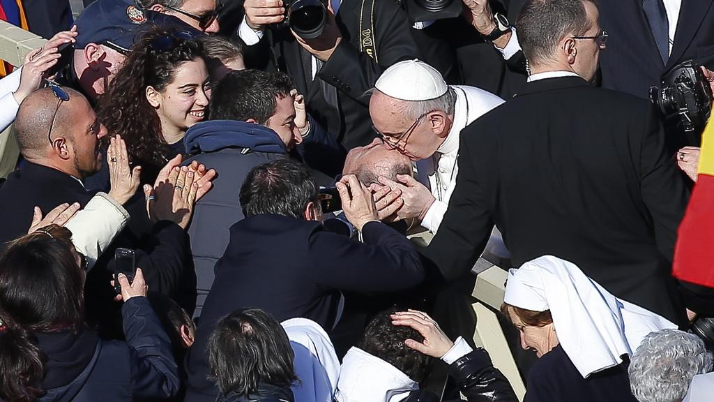 Papež líbá postiženého muže na Svatopetrském náměstí