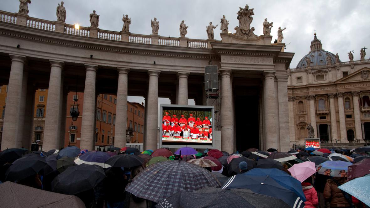 Věřící na Svatopetrském náměstí sledují shromáždění kardinálů
