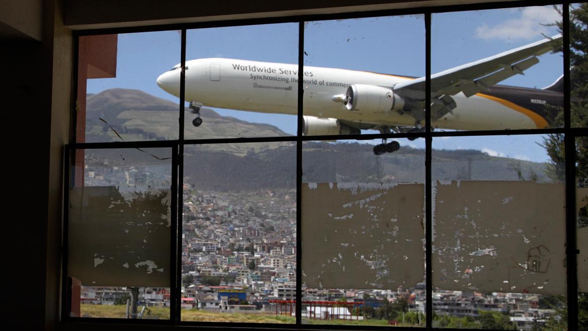 Pohled na přistávající letadlo z oken školy v Quitu
