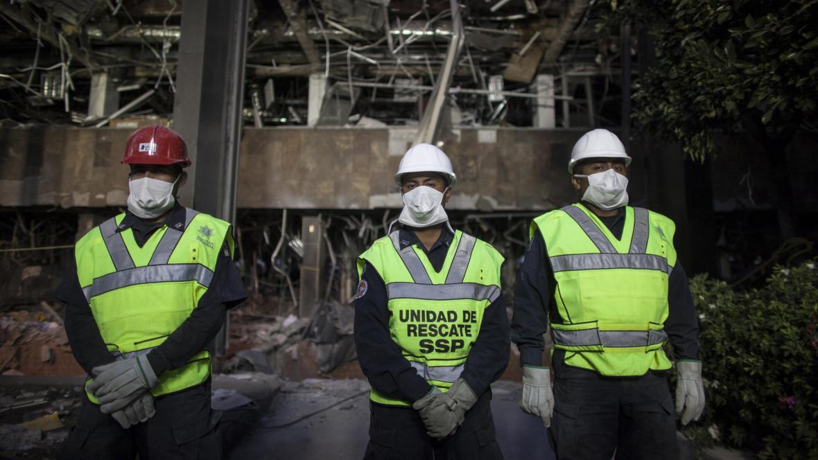 Záchranáři před zdevastovaným sídlem Pemexu