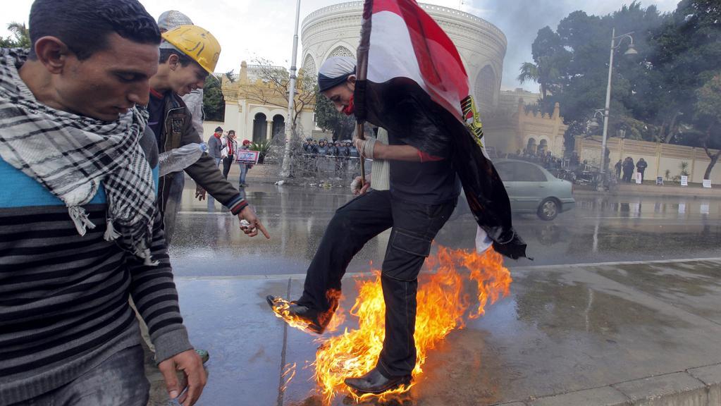 Účastník demonstrace se snaží uhasit poté, co zapálil Mursího vlajku i sebe
