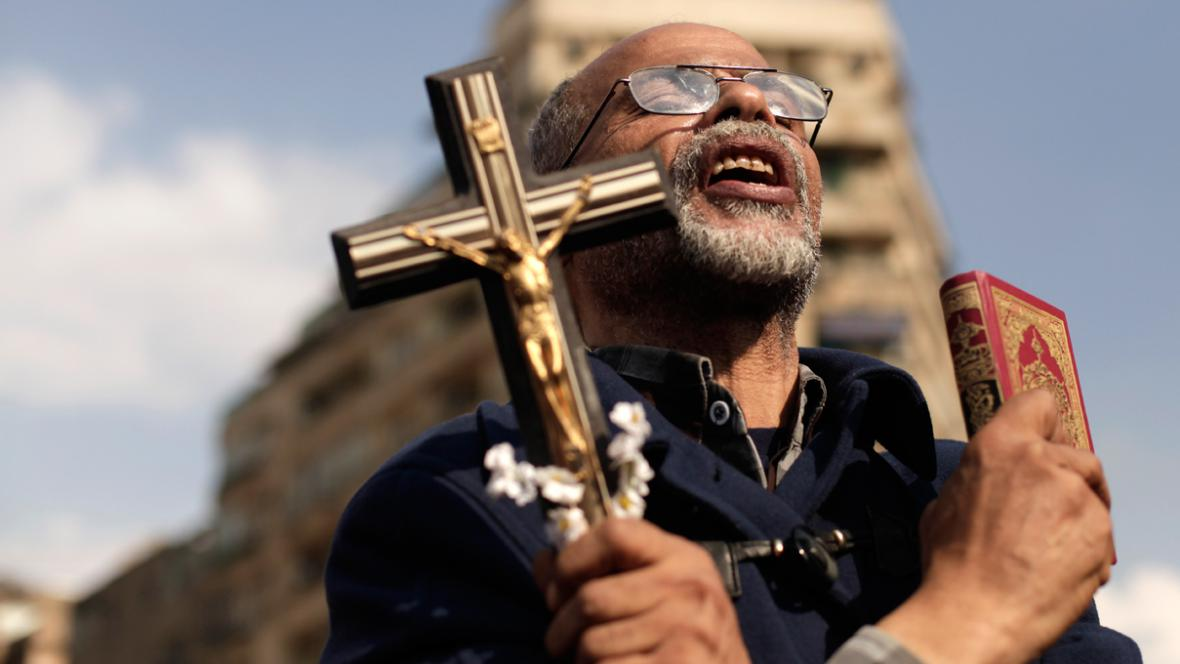 Egyptský demonstrant s křížem a koránem