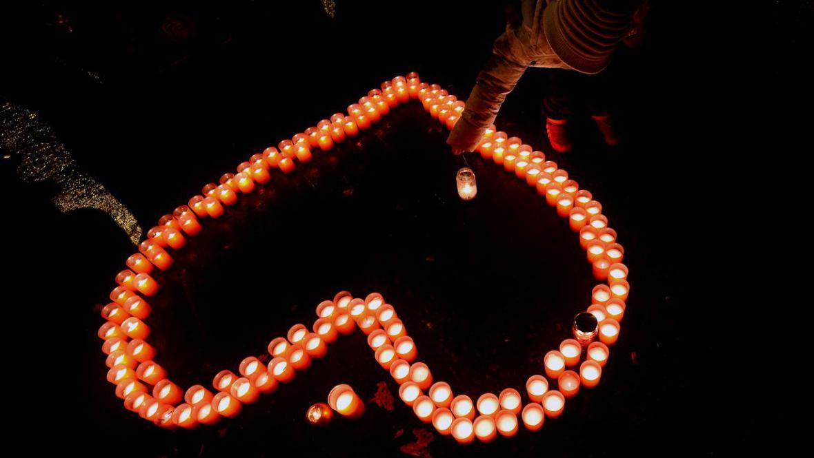 Lidé zapalují svíčky