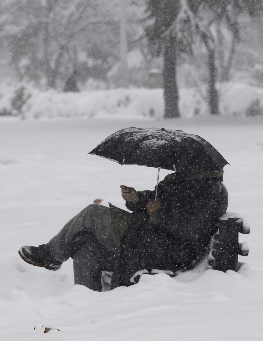 Muže v Bělehradu neodradilo od posezení v parku ani silné sněžení