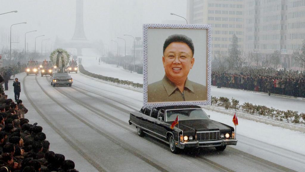 Pohřební vůz s obřím portrétem Kim Čong-ila