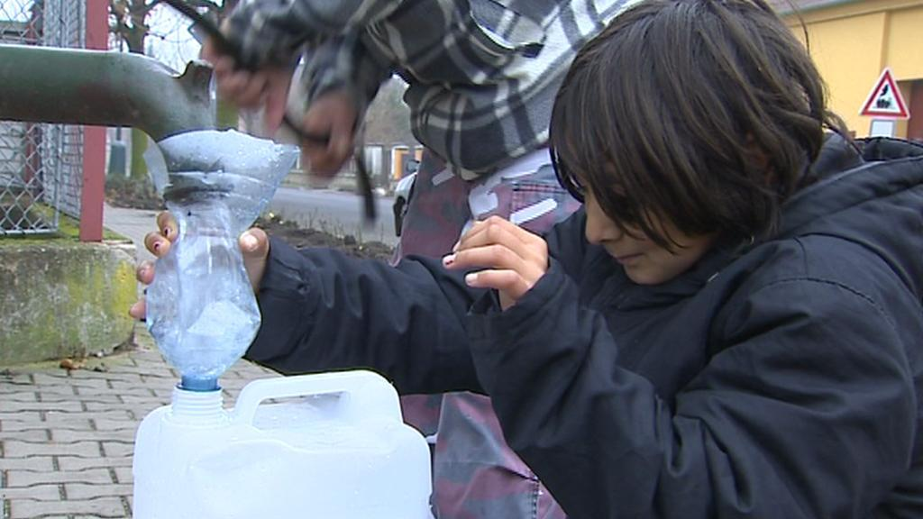 Lidé čerpají vodu z obecní studny