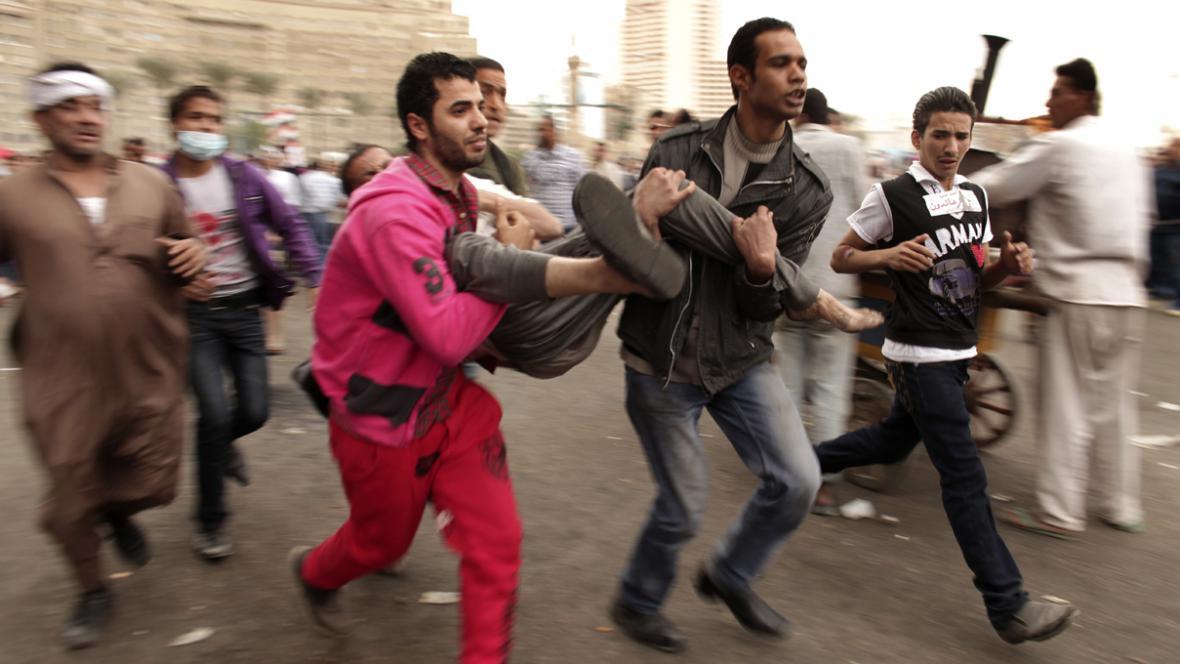 Egyptští demonstranti odnášejí zraněného kamaráda