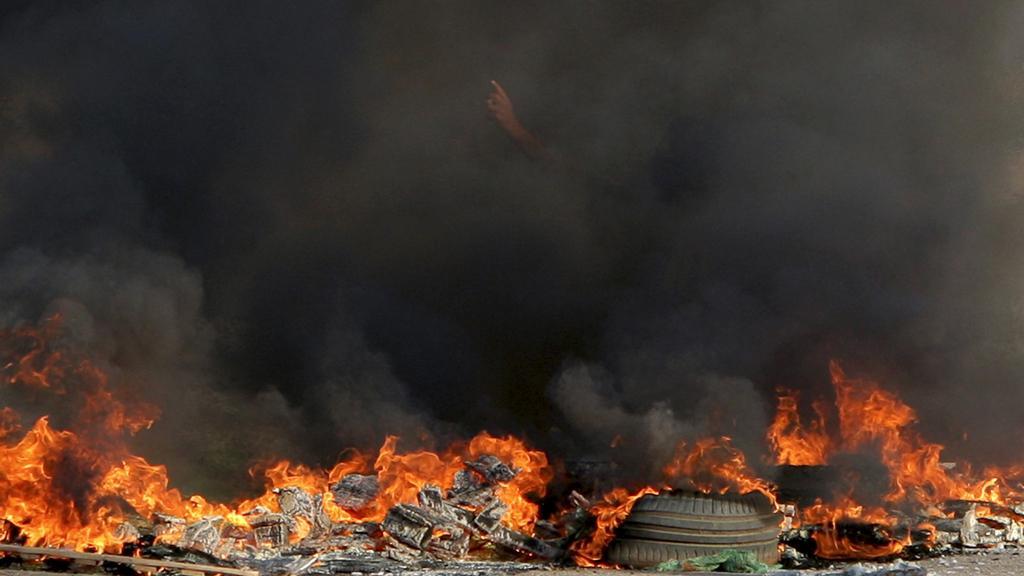 Palestinec uprostřed hořící barikády