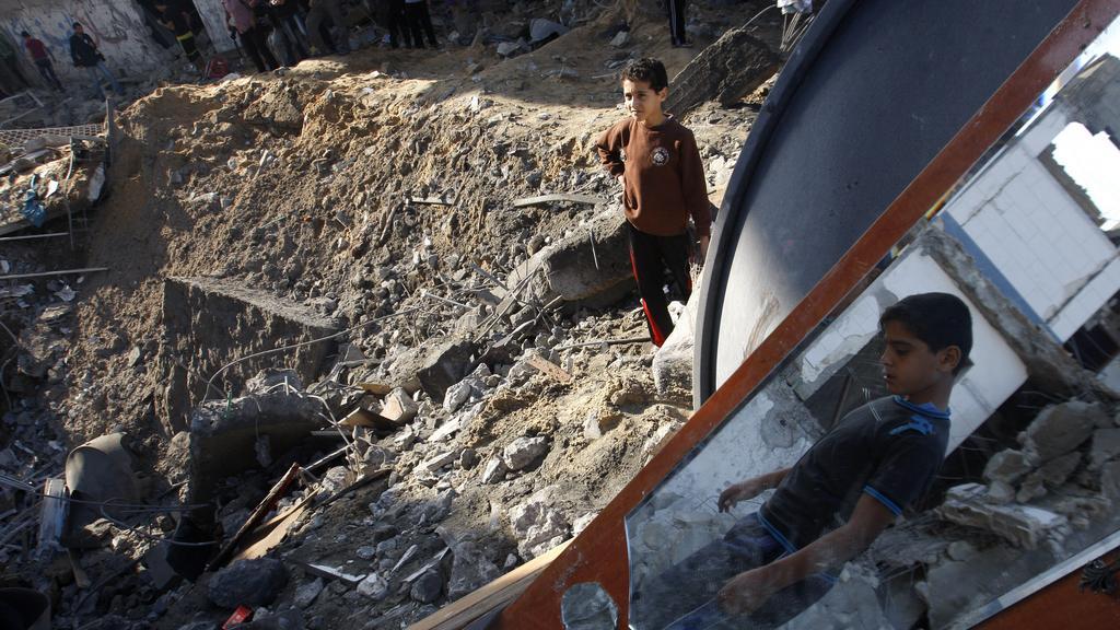 Palestinské děti stojí na troskách domu zničeného izraelskou střelou
