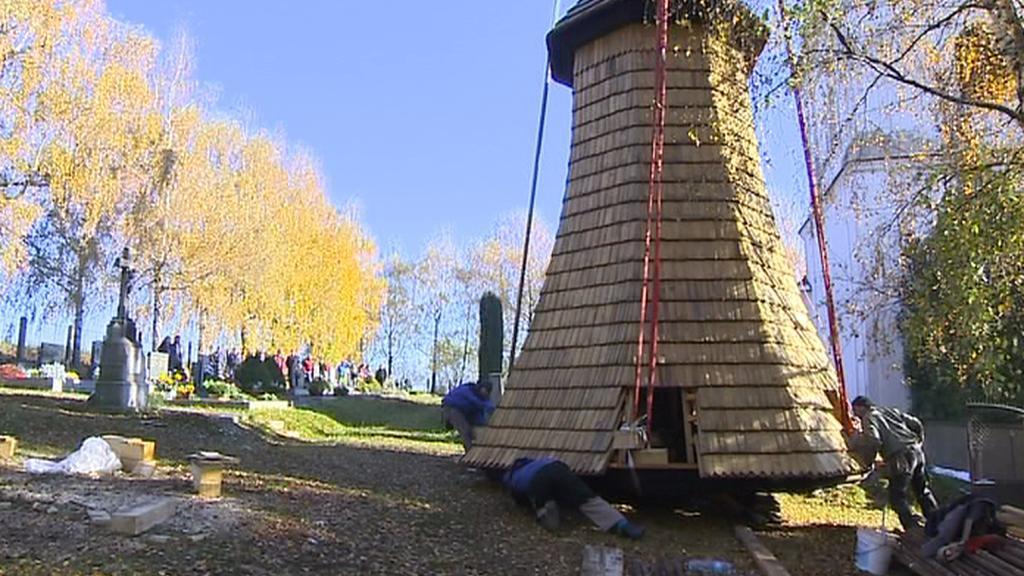 Tesaři upevňují věž kostela na jeřáb