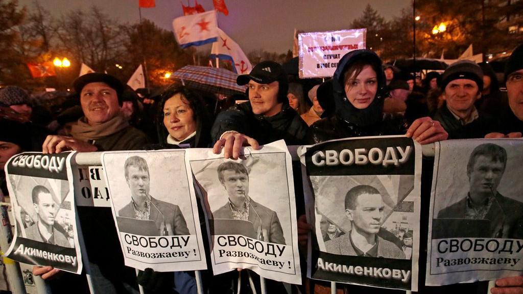 Demonstranti drží portréty zadržovaných aktivistů