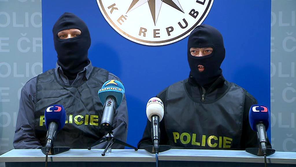 Zakuklení policisté na tiskové konferenci k akci