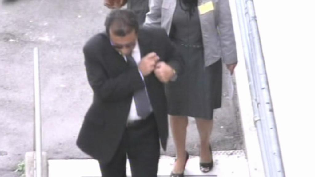 Kapitán Schettino míří vedlejším vchodem k soudu