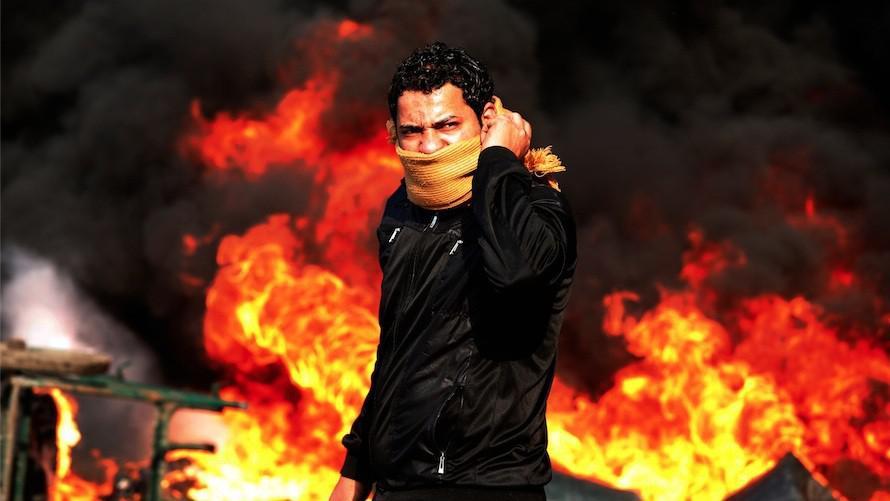 Demonstrant před hořící barikádou v Káhiře