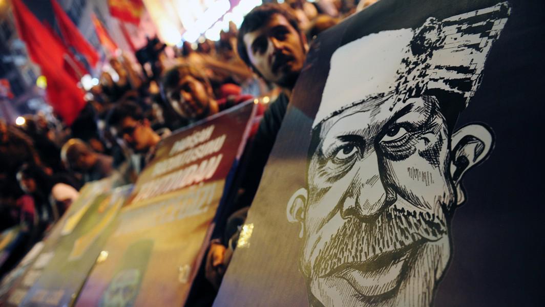 Turkové drží karikaturu premiéra Recepa Tayyipa Erdoğana během protestu proti spuštění války se Sýrií