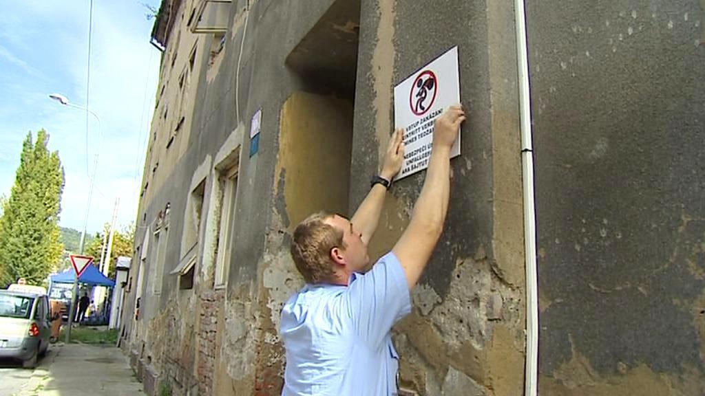 Strážník vyvěšuje na dům ceduli Zákaz vstupu